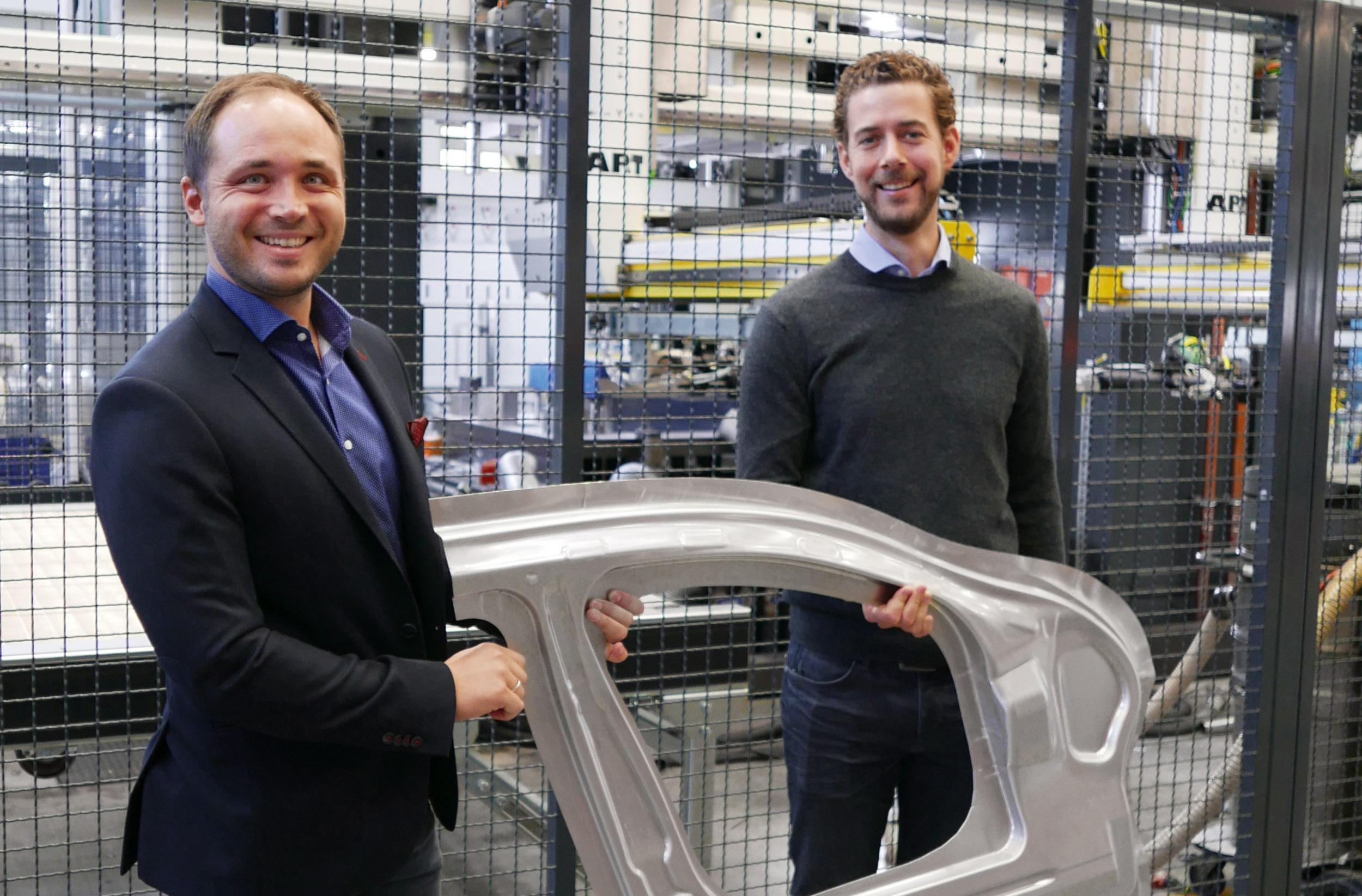 AP&T's Chief Technology Officer, Dr. Christian Koroschetz and Manager Development Forming Processes & Tooling, Dr. Michael Machhammer proudly display the complex-shaped door ring component, exhibiting the typical door inner design elements.